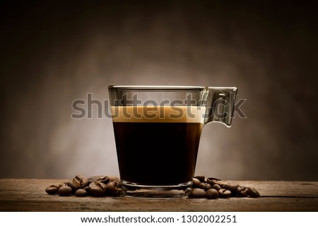 Black coffee in glass cup with coffee beans on wooden table #1302002251