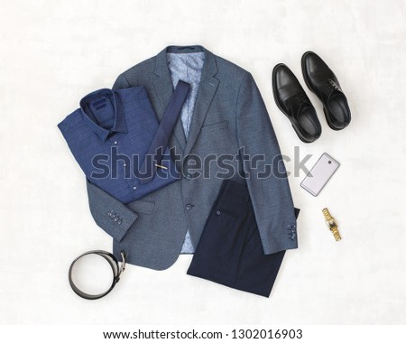 Suit jacket, pants, blue shirt, black shoes, belt, watch, necktie, smartphone. Overhead view of classic elegant formal men's outfit. Set of stylish men's clothes and accessories. Flat lay, top view. #1302016903