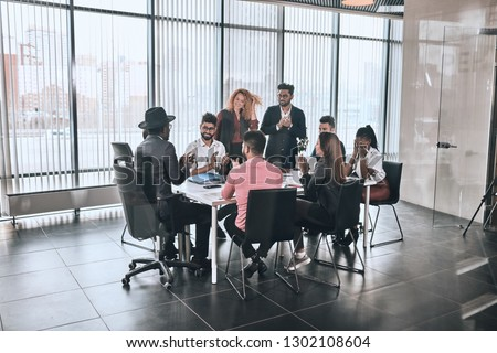 company is greeting foreign partner. happy diverse people are sitting at the table and clapping hands in the room with panorama window #1302108604