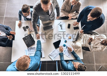 happy business people shaking hands. top view photo. agreement. office workers are greeting each other #1302111499