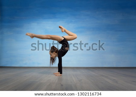 Girl gymnast in a black gymnastic swimsuit makes handstand on a blue sky background. #1302116734
