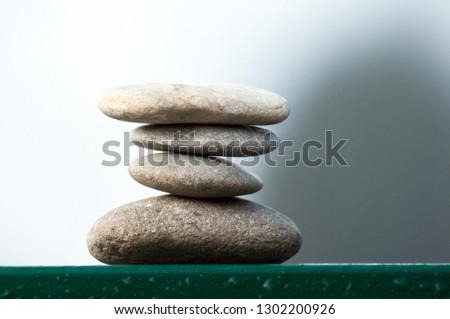 Closeup of stone balance on metallic fence in border river #1302200926