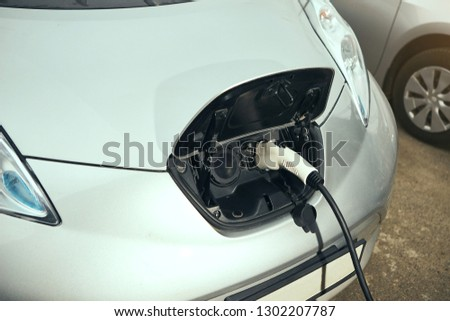 Electric car at charging station with the power cable supply plugged . Eco-friendly alternative energy concept #1302207787