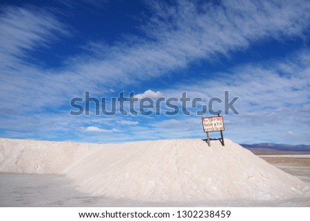 A snow white pile of salt in the Salinas Grandes, a salt flat in northern Argentina, lying under blue sky and scenic clouds. The warning sign says: Please do not climb on the pile of salt. #1302238459