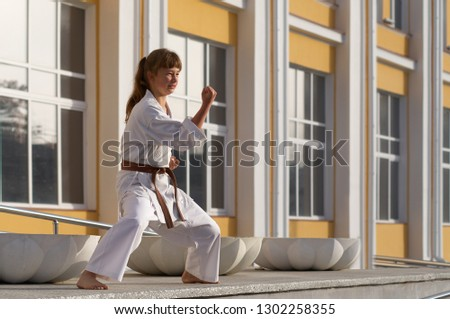 Young Woman in Kimono doing formal karate exercising on cityscape background #1302258355