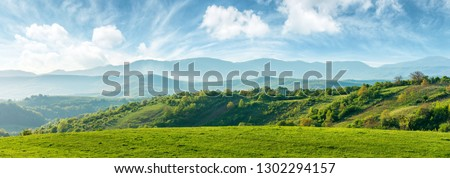 panorama of beautiful countryside of romania. sunny afternoon. wonderful springtime landscape in mountains. grassy field and rolling hills. rural scenery #1302294157