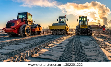 roller compacts soil in embankment on the road's construction. sand consolidation on road-building. Compactor driving on sandy. wheel marks on the sand. hard work. transportation of sand by trucks Royalty-Free Stock Photo #1302301333