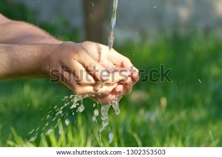 summer in the country. men's hands under the pressure of water in the garden. #1302353503