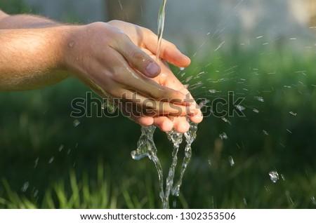 summer in the country. men's hands under the pressure of water in the garden. #1302353506