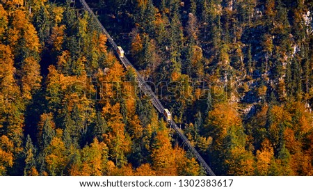 Beautiful aerial fall view of cable car ropeway funicular in austrian alps. Red cable railway car in the mountains by resort village Hallstatt, Salzkammergut, Austria, Alps. #1302383617