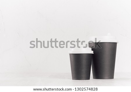 Coffee mockup - big and small blank black paper cups with white cap on white wood table with copy space, coffee shop interior. Modern elegant concept for branding identity, advertising, design. #1302574828
