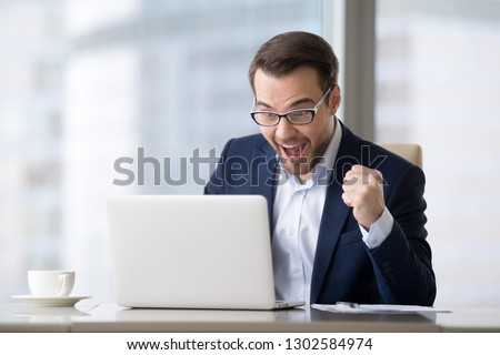 Excited businessman in suit feeling winner celebrating online victory business success watching game at work looking at laptop, happy male executive ceo received good news, winning bet bid results #1302584974