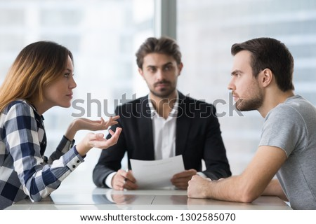 Annoyed unhappy married couple arguing in lawyers office get divorced, angry family spouses split up having disagreement disputing about breaking up and divorce settlement, legal separation concept Royalty-Free Stock Photo #1302585070