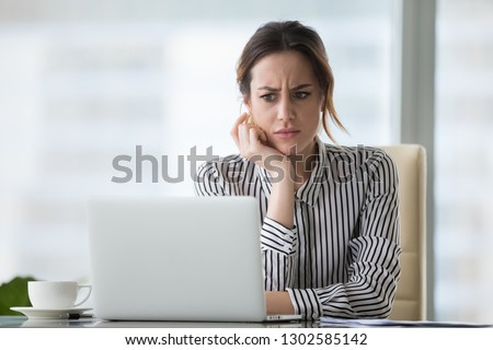 Confused businesswoman annoyed by online problem, spam email or fake internet news looking at laptop, female office worker feeling shocked about stuck computer, bewildered by scam message or virus #1302585142