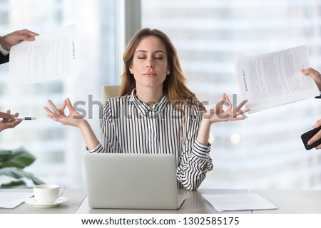 Calm female executive meditating taking break at work for mental balance, mindful businesswoman feeling relief and no stress doing yoga at work ignoring avoiding stressful job and paperwork in office #1302585175