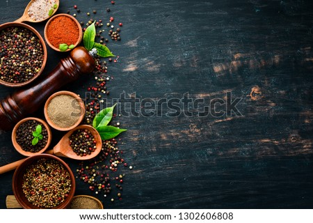 A set of peppers. Black pepper, colored pepper, ground pepper, dried chili pepper. Top view. On a black background. free space for your text. #1302606808