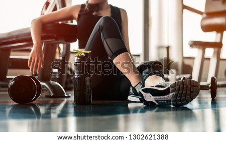 Fitness woman Relaxing after exercise with a whey protein and dumbbell placed beside the gym.Relaxing after training.beautiful young woman looking away while sitting  at gym. #1302621388