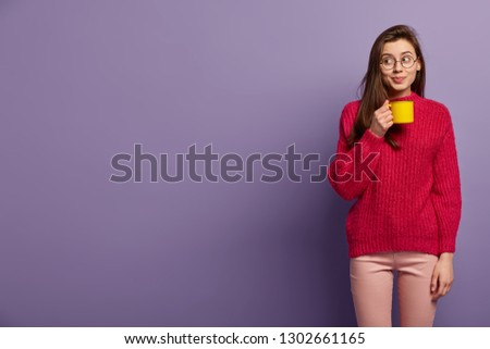 Satisfied young college student holds yellow mug with hot drink, wears spectacles, red warm sweater, focused aside, notices something, poses over lilac backround with empty space for your advert #1302661165