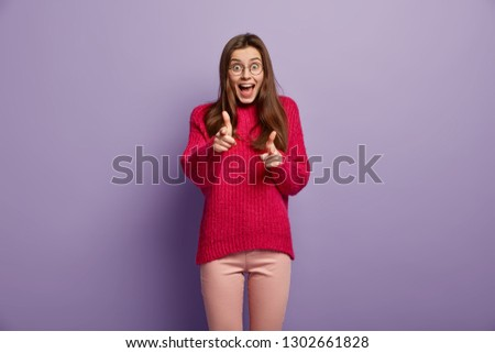 Horizontal view of joyful happy dark haired woman makes finger gun gesture, indicates at you, dressed in red jumper and trousers, poses over violet background, expresses choice. Bang, you are killed #1302661828