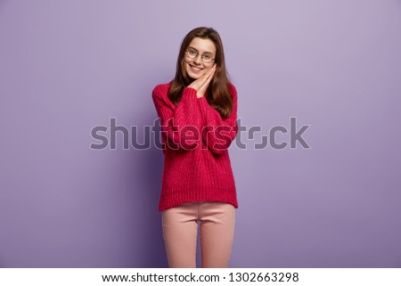 Indoor shot of pleased dark haired woman leans at palms, has tender smile, hears something pleasant, wears red knitted sweater, trousers and round spectacles, stands against purple background #1302663298