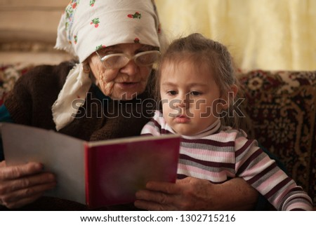 grandmother with their child granddaughter sitting on sofa at home and read a book #1302715216