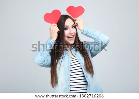 Beautiful woman holding red paper hearts on grey background #1302716206