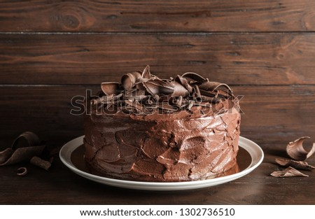 Plate with tasty homemade chocolate cake on wooden table #1302736510