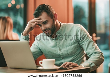 Attractive businessman using a laptop and thinking what is going wrong, while working in café. #1302758266