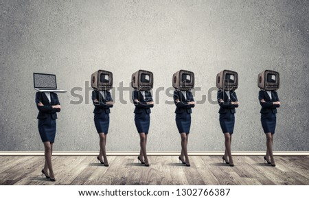 Business women in suits with old TV instead of their heads keeping arms crossed while standing in a row and one at the head with laptop in empty room against gray wall on background. #1302766387