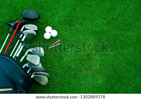 Golf ball and golf club in bag on green grass #1302889378