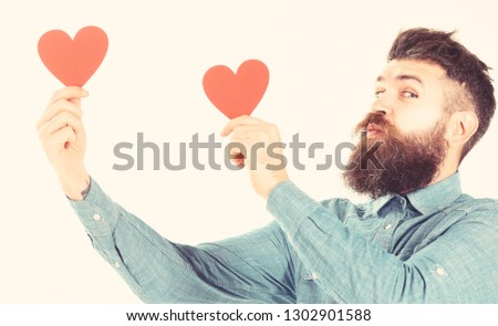 Macho celebrates valentines day. Hipster sends or receives valentine cards. Romantic feelings and love concept. Man with beard and kissing face hold red hearts isolated on white background. #1302901588