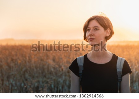 Backlit portrait of a woman in sunset. Female person standing in evening sunlight at a field
