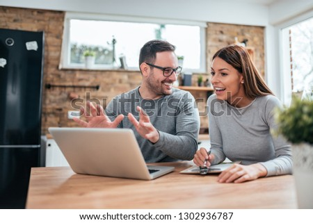 Positive young couple looking at laptop and talking. #1302936787