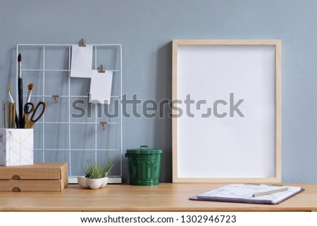 Home office interior with mock up poster frame on the brown wooden table with office accessories, paper box, air plant in design pots, notebook and notes. Grey walls. Minimal concept of mockup. #1302946723