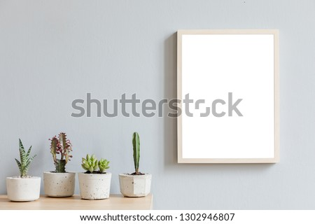 Minimalistic room interior with mock up photo frame on the brown wooden table with beautiful plant in design hipster pot. Grey walls. Stylish and floral concept of mock up poster frame.