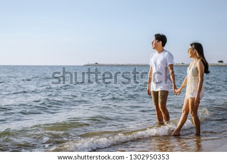 Asian couple are happy with love on the beach at summer weekend holiday. #1302950353