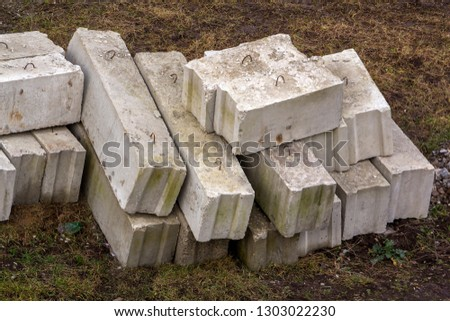 Stack of rough natural brown uneven different sizes and forms stone concrete cement blocks for foundation or wall construction on dirty ground background. #1303022230