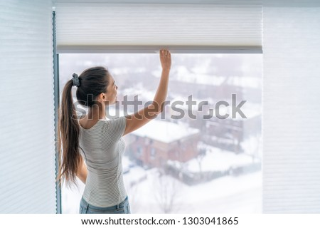 Home blinds window shades woman opening shade blind during winter morning. Asian girl holding modern cordless top down luxury curtains indoors. #1303041865