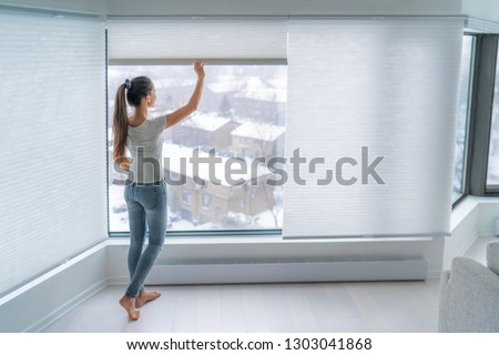 Woman closing cellular shades on apartment window keeping energy and heat indoors with honeycomb blind curtain. Cordless pleated shades in modern home living lifestyle. Interior decor design. #1303041868