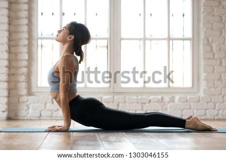 Young sporty woman practicing yoga, doing upward facing dog exercise, Urdhva mukha shvanasana pose, working out, wearing sportswear, pants and top, indoor full length, white yoga studio #1303046155
