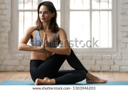 Young attractive woman practicing yoga, doing Half lord of the fishes exercise, Ardha Matsyendrasana pose with namaste , working out, wearing sportswear, pants and top, indoor full length, yoga studio #1303046203