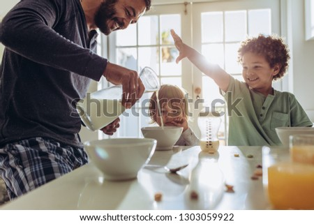 Father making breakfast for his kids at home. Man having fun preparing breakfast at home with his kids. #1303059922