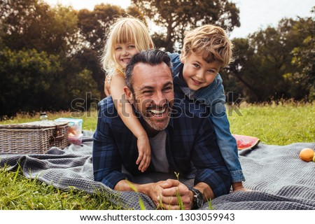 Happy man with kids on a picnic lying down in park beside a picnic basket. Children lying on the back of their father. #1303059943