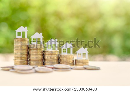 Home loan / reverse mortgage, asset refinancing concept : Small house or home on stacks of coins, depicts a homeowner or a borrower turns properties into cash, saving money to buy shelter, basic need #1303063480