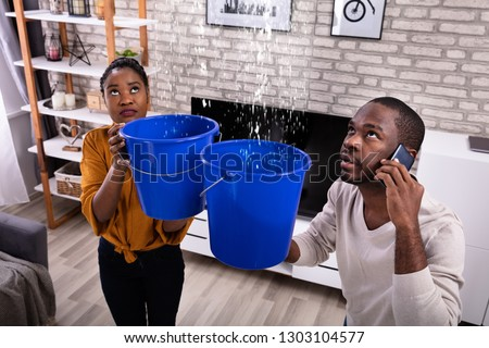 Couple Using Bucket For Collecting Water Leakage From Ceiling And Calling Plumber On Cellphone Royalty-Free Stock Photo #1303104577
