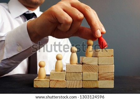 Job Promotion. Manager is holding figurine near career ladder. Worker raises. #1303124596
