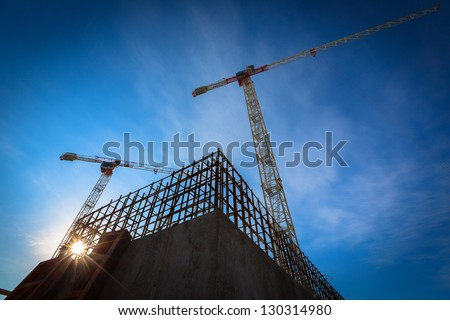 Construction site with cranes on sky background Royalty-Free Stock Photo #130314980