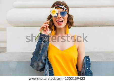 stylish attractive woman in hippie style outfit, yellow dress denim jacket, trendy accessories, sunglasses, smiling, holding flower, street fashion, spring summer fashion trend, laughing, emotional #1303159423