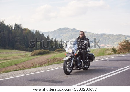 Handsome motorcyclist in black leather outfit riding cruiser bike on bright sunny summer day on background foggy distant green woody hills under morning sky. #1303200697