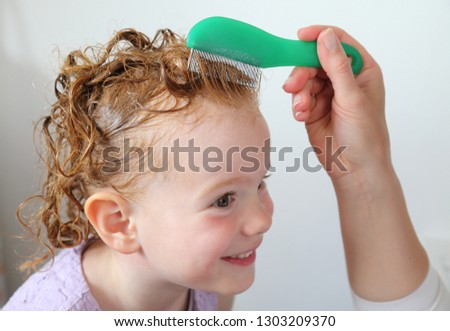 A Lice louse comb in girls hair